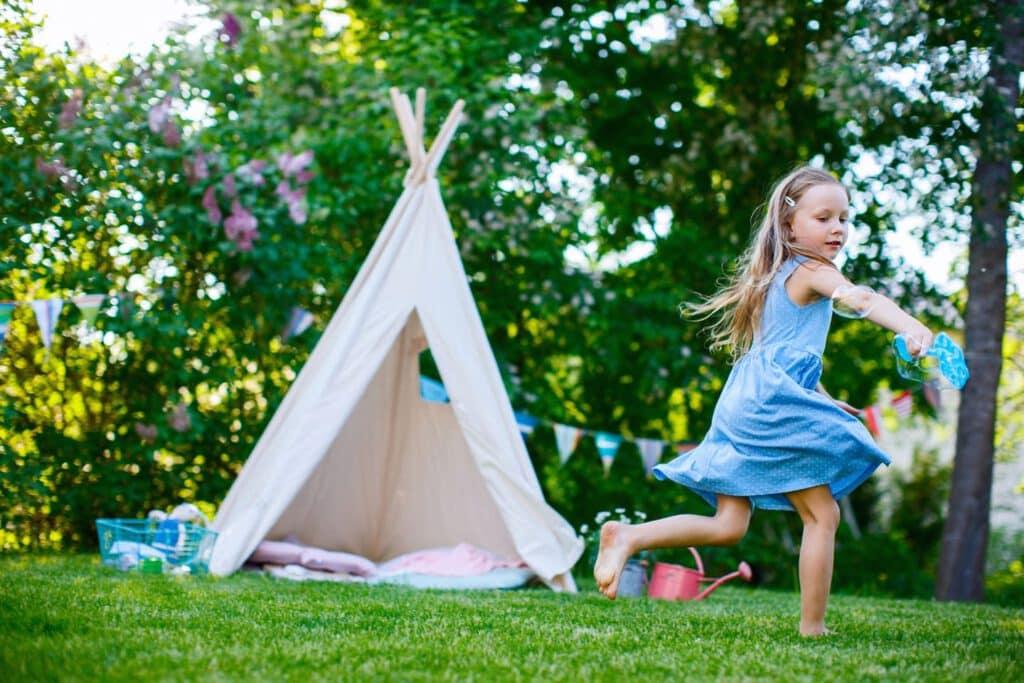 Tipi Garten. Vor einem Tipi Zelt im Garten spielt ein kleines Mädchen